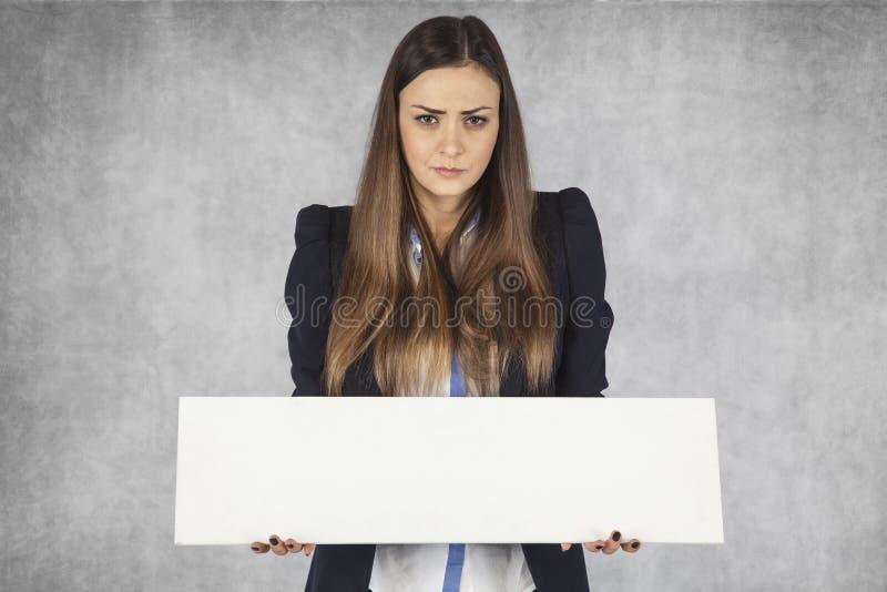 恼怒的女商人拿着您的广告的一个地方,站立灰色背景的 库存图片