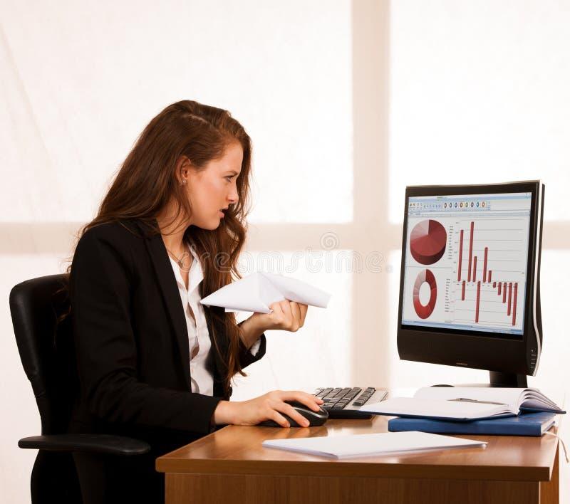 恼怒的女商人表现出愤怒在她的书桌用办公室 库存照片