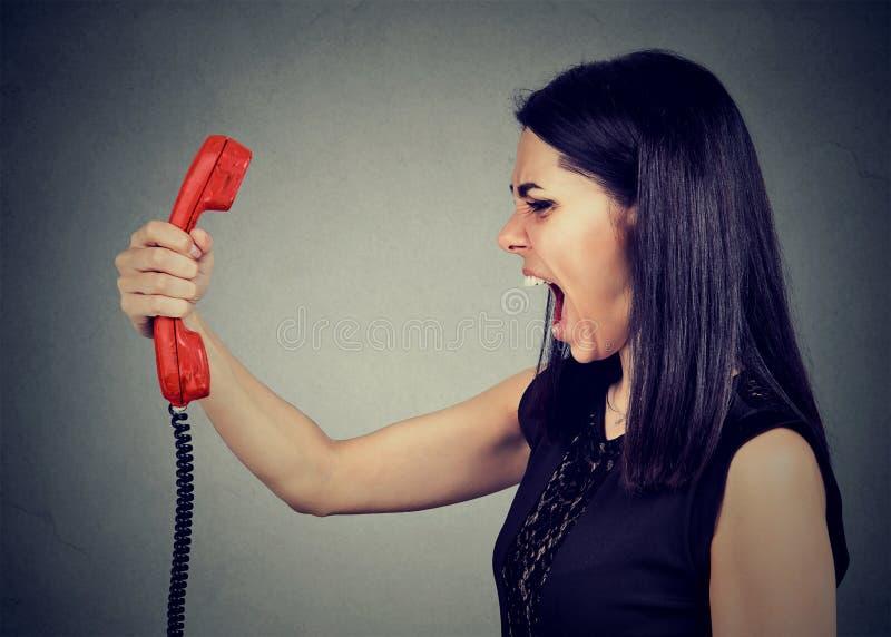 恼怒的妇女叫喊对电话 免版税图库摄影