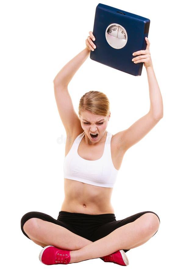 恼怒的妇女秤 减肥减重 库存图片