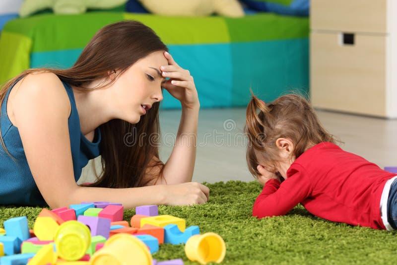 恼怒的婴孩和疲乏的母亲在屋子里 免版税库存照片