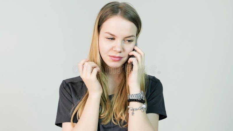 恼怒的少妇,啼声,与她的手机,美丽的女孩混淆,哀伤,紧张,翻倒,重音和认为 库存照片