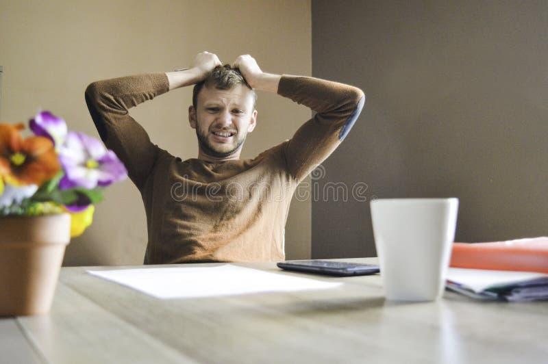 恼怒的年轻人和哀伤的工作坚硬在文书工作和票据在家 库存图片