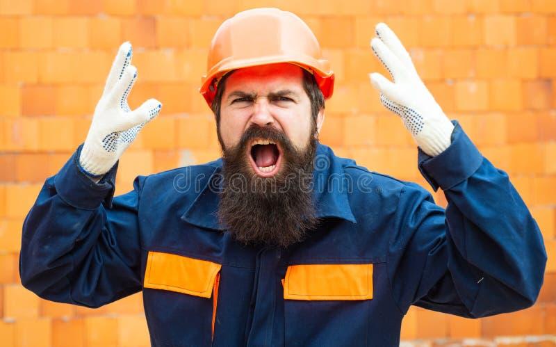 恼怒的建造者 在工地工作的事件 建造者的安全规则 盔甲的有胡子的人在建筑  免版税库存照片