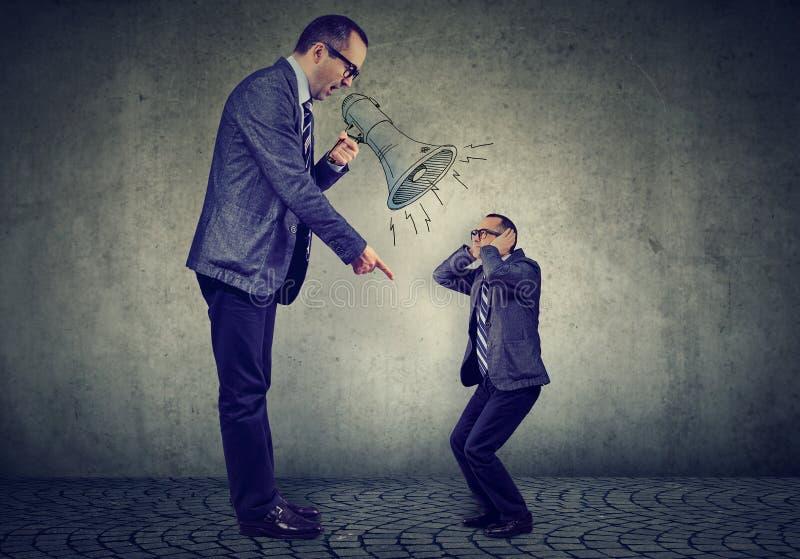 恼怒的成熟的商业人上司尖叫对小他自己在扩音机 免版税库存照片