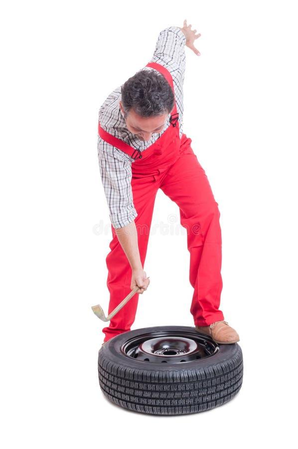 恼怒的技工改变的轮胎 库存照片