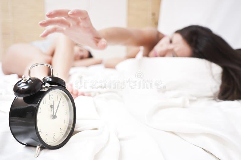 恼怒的时钟敲响的休眠终止妇女 库存照片