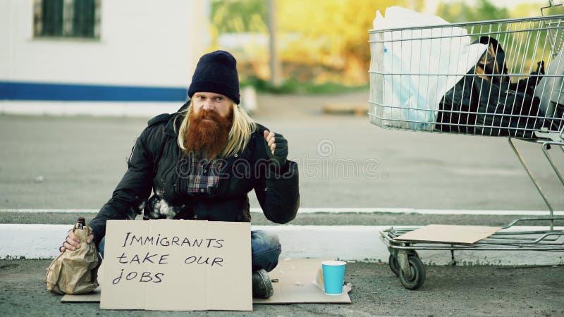 恼怒的有坐在购物车和饮料酒精附近的纸板的翻倒年轻无家可归的人冷的天由于 免版税库存照片