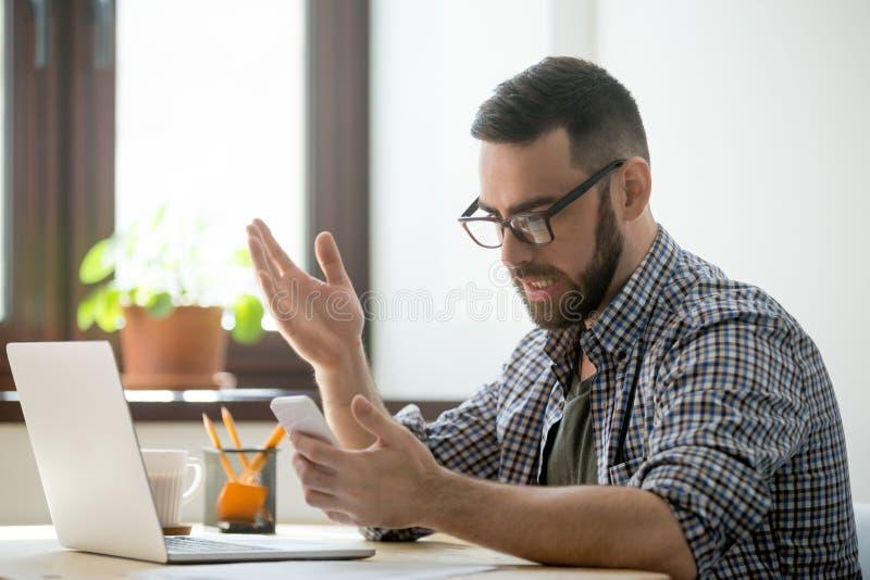 恼怒的有胡子的商人懊恼了与电话在办公室 库存图片