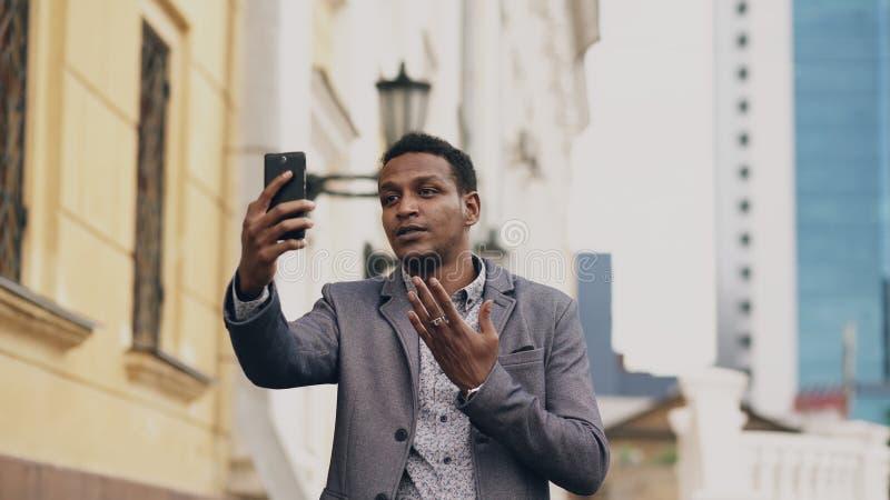 恼怒的混合的族种商人有网上录影闲谈在业务会议使用智能手机 免版税库存图片