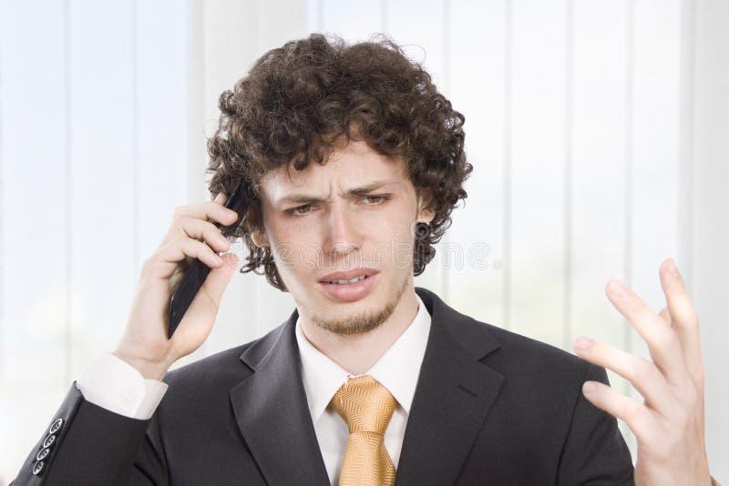 恼怒的生意人解释电话 免版税库存照片