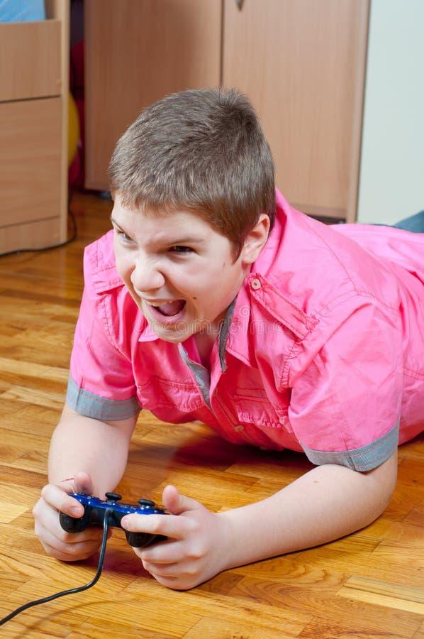 恼怒的男孩胖电脑游戏使用少年 库存照片