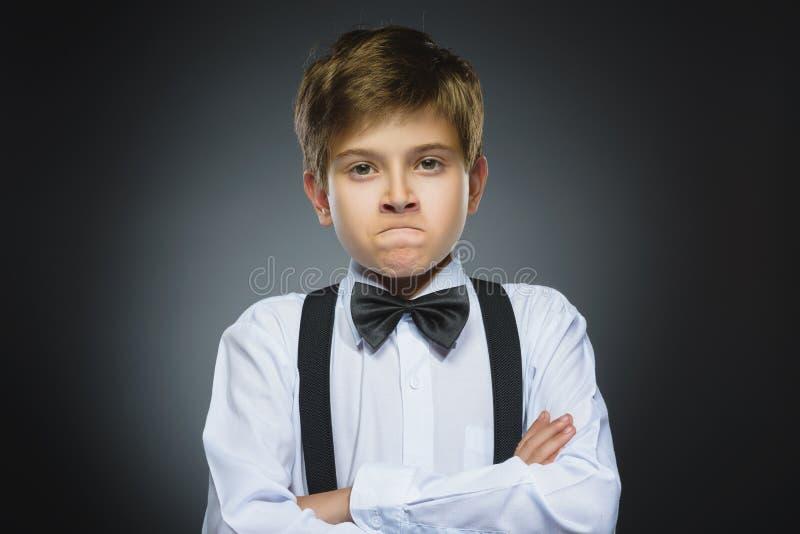 恼怒的男孩画象灰色背景的 消极人的情感,表情 特写镜头 免版税库存照片