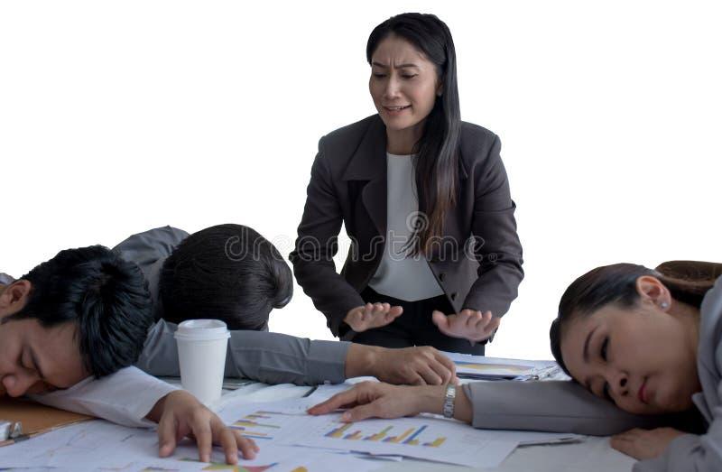 恼怒的睡觉在办公室的上司观看的雇员,因为劳累过度与在白色背景的许多孤立 免版税图库摄影