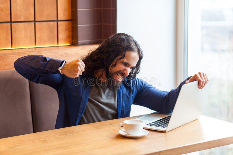 恼怒的积极的年轻成人人自由职业者画象设法的便装样式的坐在咖啡馆和碰撞膝上型计算机屏幕,上升了 库存照片