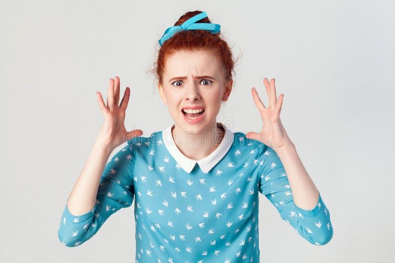 年轻恼怒的红头发人女孩画象看恐慌的蓝色礼服的,尖叫秘密审议与嘴的大开,用手 库存图片