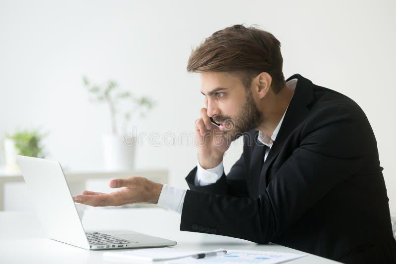 恼怒的经理谈话在解决公司问题的电话 库存图片