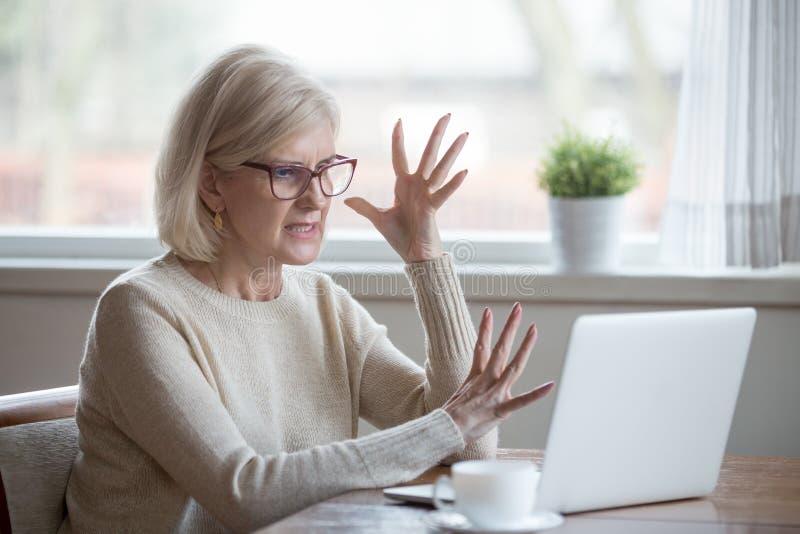 恼怒的被注重的中部年迈的女商人懊恼了与计算机 免版税库存图片