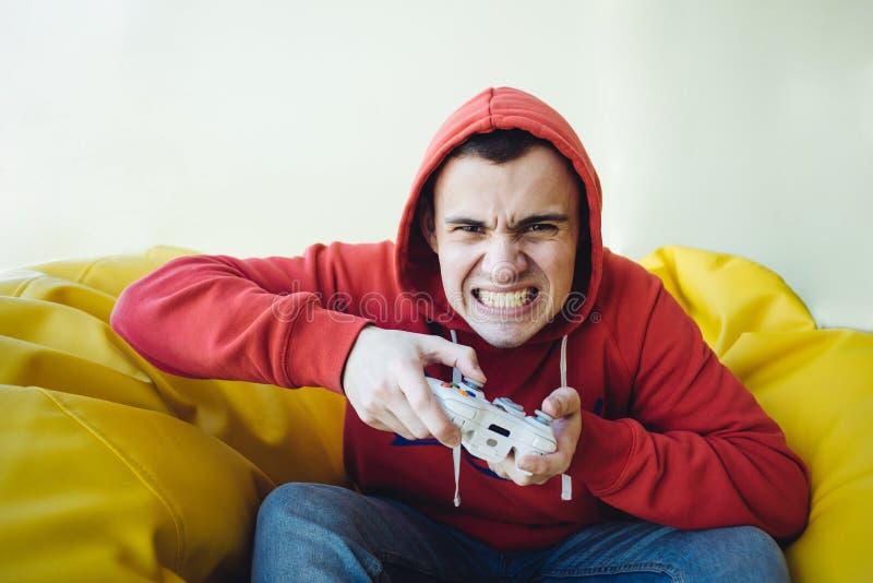 恼怒的青少年的游戏玩家情感地播放在控制台的一根控制杆 照相机的被聚焦的看法 免版税库存照片