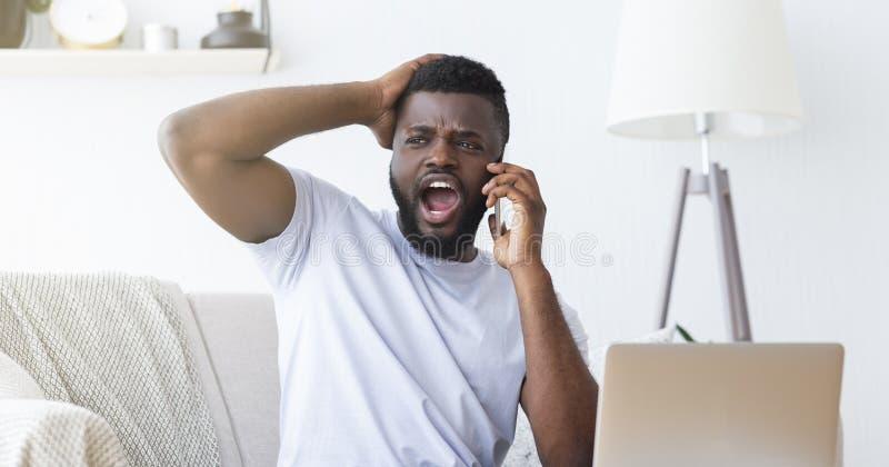 恼怒的非裔美国人的人谈话在手机 免版税库存照片