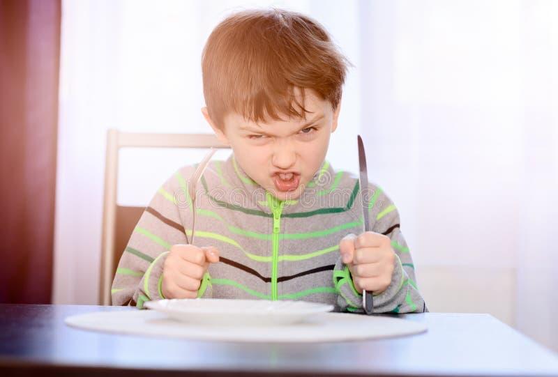 恼怒的饥饿的男孩儿童等待的晚餐 库存照片