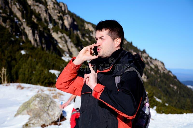 恼怒的年轻人画象谈话在冬天山的电话 库存照片