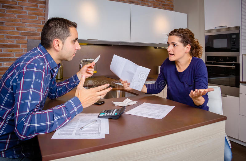 恼怒的年轻夫妇争论由信用卡债务 库存照片