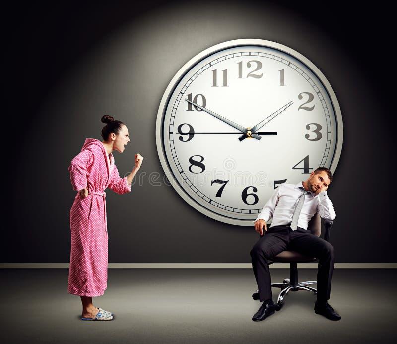 恼怒的妻子尖叫对懒惰丈夫 免版税库存图片