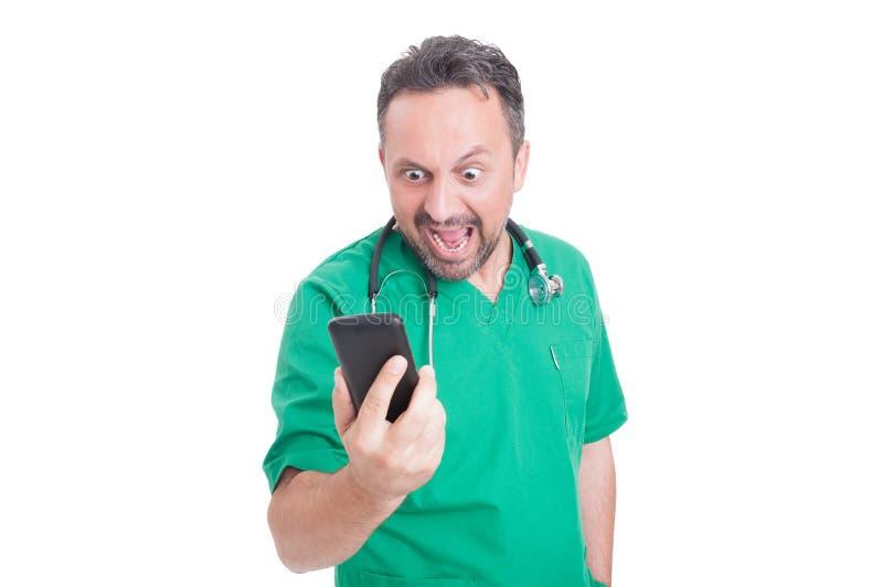 恼怒的医生看和叫喊他的智能手机 免版税库存照片