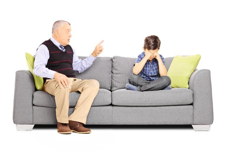 恼怒祖父呼喊在他的侄子,安装在沙发 库存照片