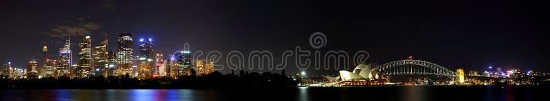 悉尼地平线的全景,包括港口桥梁和歌剧院在晚上 库存图片