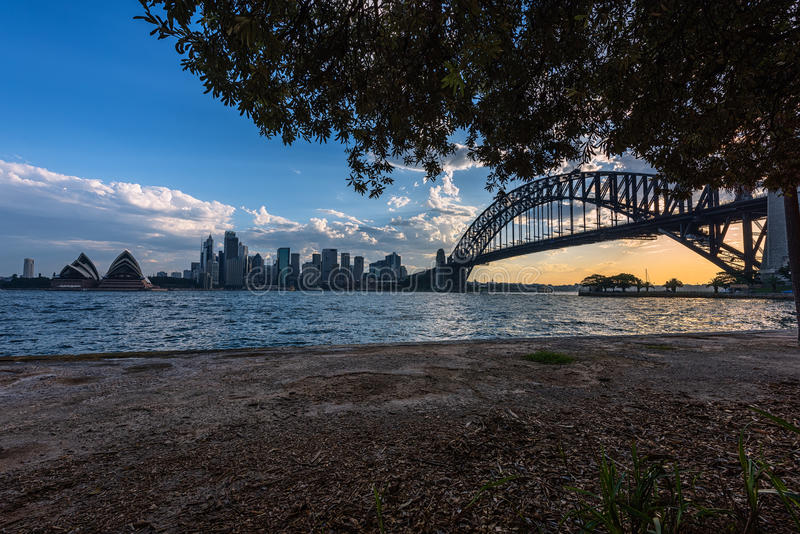悉尼歌剧院和港口桥梁日落的悉尼澳大利亚看法  免版税库存图片