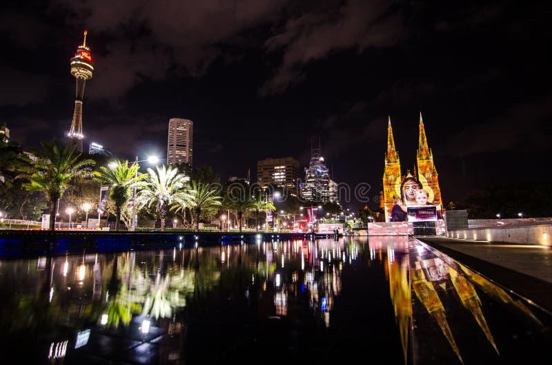 悉尼都市风景夜摄影与`的圣诞节`光是年会由在圣玛丽教会的投射照明设备 库存图片