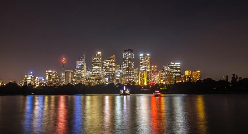 悉尼都市风景看法在黄昏的横跨从植物的雀鳝的港口 免版税库存照片
