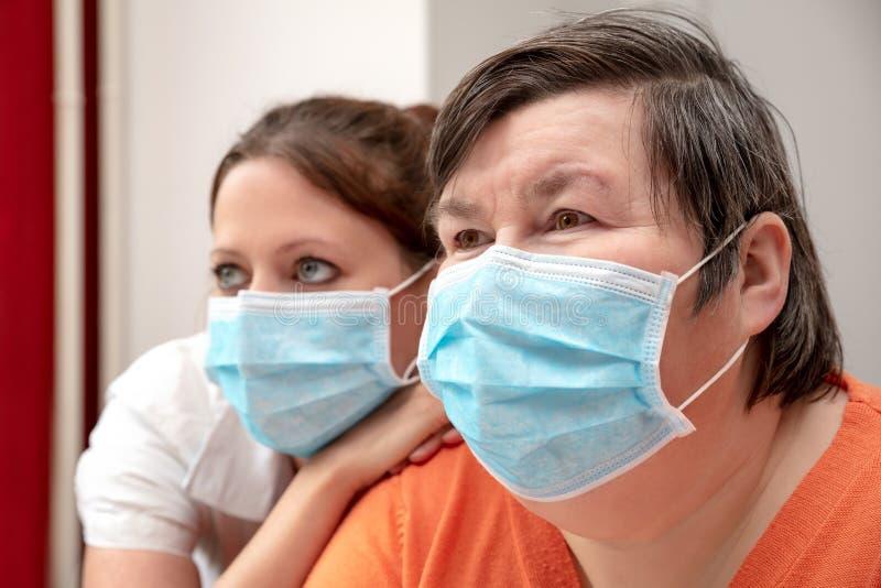 患有精神障碍的妇女、护士或看护人,戴着外科面具、Covid-19或电晕 库存图片