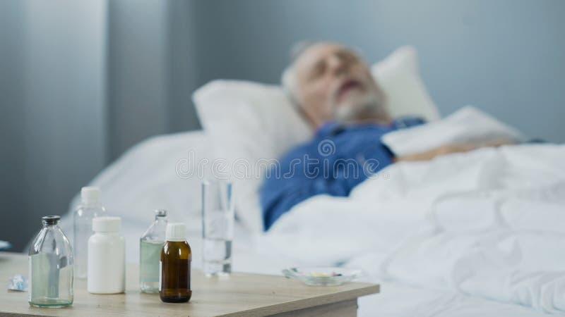 患绝症男性睡觉在采取止痛药以后,疗程的医院 免版税库存图片