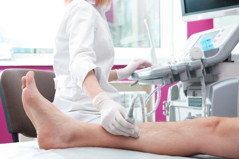 患者的腿的医生举办的超声波考试在诊所的 库存照片