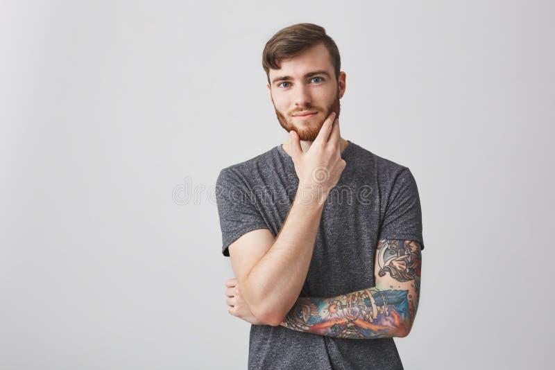 悦目不剃须的人画象有黑发和被刺字的手的在灰色衬衣感人的胡子用手,看 免版税库存照片