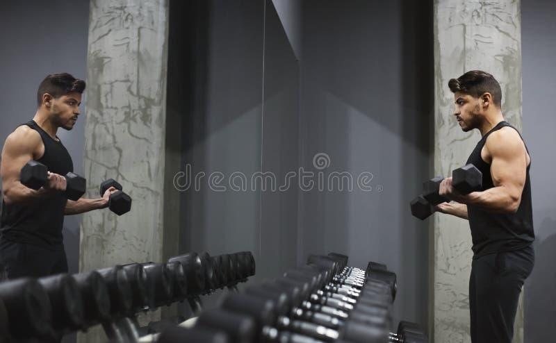 悦目在镜子前面的年轻人举的哑铃 库存图片