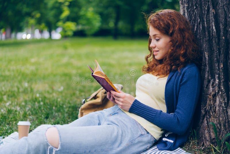 悦目少女看书和微笑的开会在草坪在公园 图库摄影