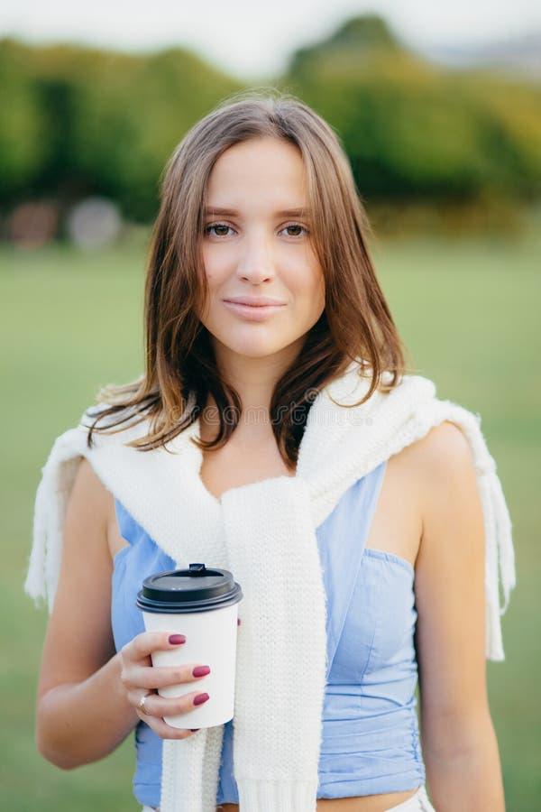 悦目年轻欧洲妇女坦率的射击有直发的,穿戴在偶然成套装备,喝外带的咖啡,有漫步 库存图片