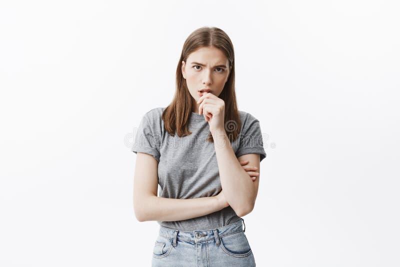 悦目年轻sudent女孩和在时髦灰色衣裳的黑发画象有中等头发长度的咬钉子  免版税库存照片
