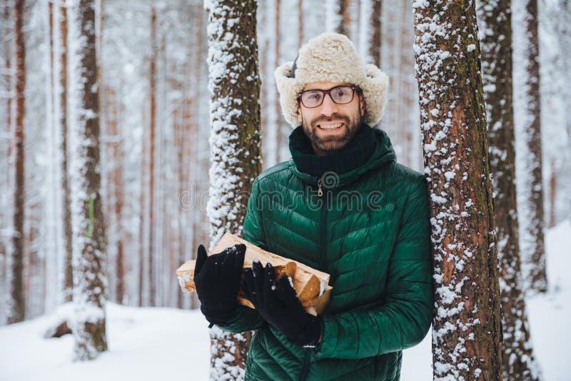 悦目微笑的男性在冬天前面穿温暖的冬季衣服拿着木柴,站立在树附近,花费与朋友的时间 免版税库存照片