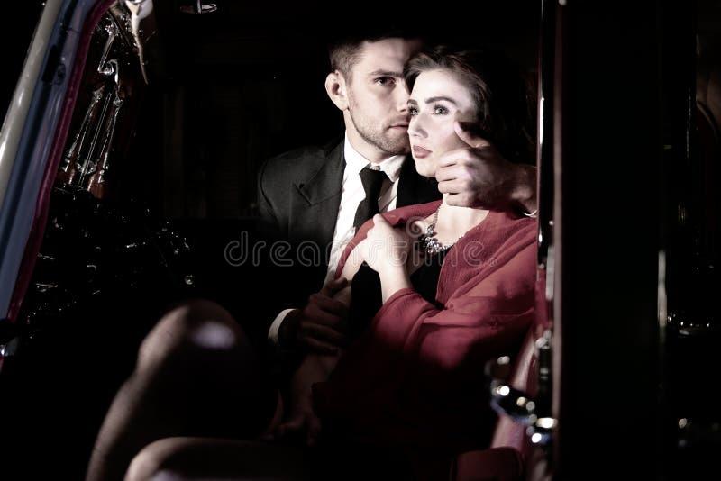 悦目性感的夫妇,衣服的英俊的人,红色礼服的美丽的妇女,在葡萄酒汽车热情地拥抱 免版税库存照片