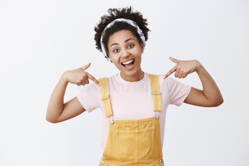悦目迷住yeloow总体和头饰带的活跃和乐观非裔美国人的女孩指向她自己的 免版税库存照片