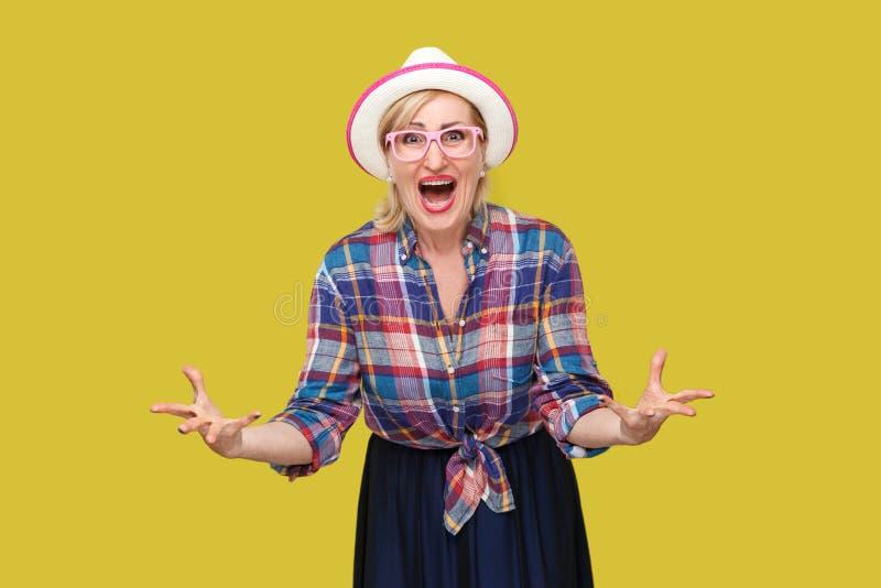 您从我想要什么?恼怒的现代时髦的成熟妇女画象便装样式的与帽子和镜片身分,看 免版税图库摄影
