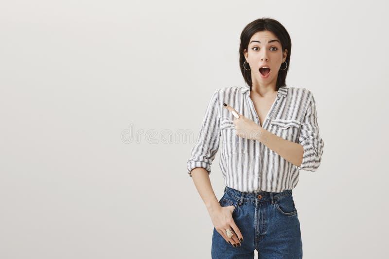 您从未相信什么我看见了 喘气的惊奇的妇女演播室射击,屏息从兴奋的,指向左 图库摄影