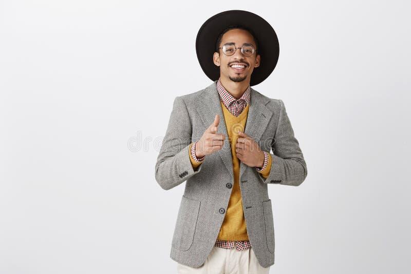 您和我,完善的组合 确信的可爱的富有的深色皮肤的人演播室画象时髦的帽子和夹克的 免版税库存图片