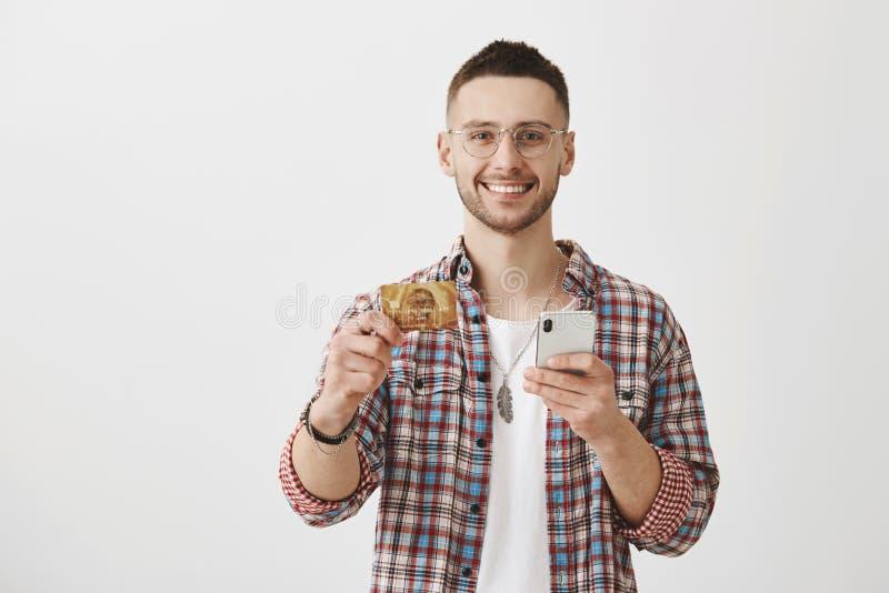 您应该得到这张卡片 拿着信用卡和智能手机的可爱的年轻工友,广泛地微笑在 免版税库存照片