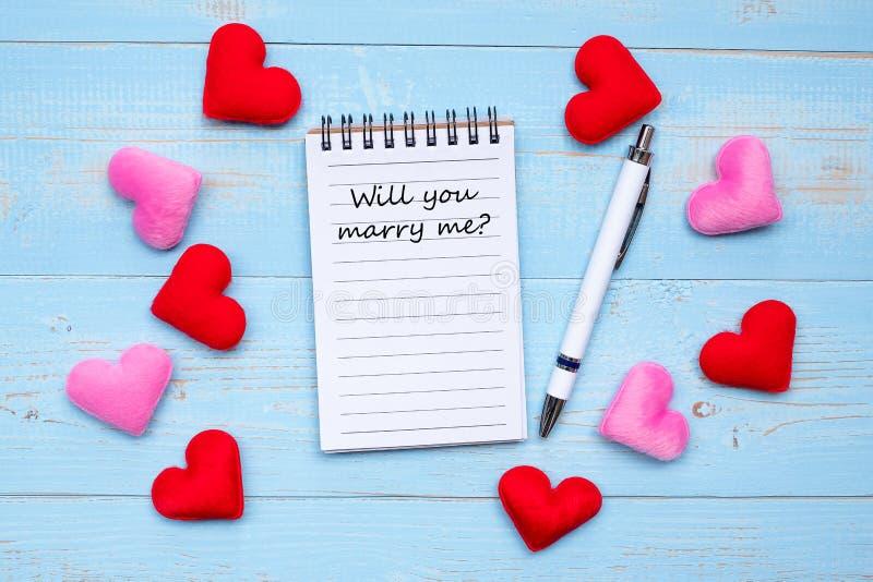 您是否与我结婚?在笔记本和笔的词与在蓝色木桌背景的红色和桃红色心形装饰 爱, 免版税图库摄影